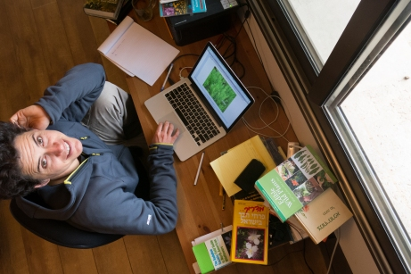 Tomer researching amongst his library of resources.