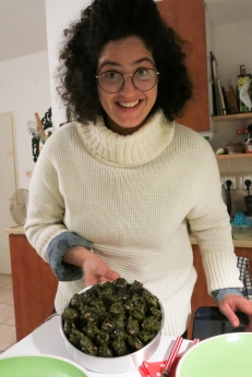 Graphic designer Noam Chen shares her stuffed grape leaf recipe during a team dinner.